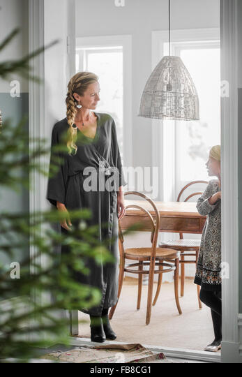 Sweden, Mother and daughter (6-7) standing in room with Christmas tree - Stock Image