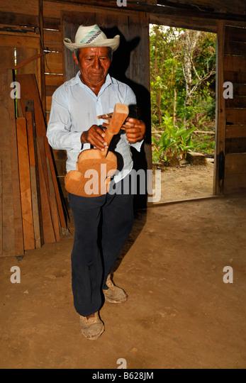 Man, native musician, tuning a home-made instrument, violin, wooden hut, Punta Gorda, Belize, Central America - Stock-Bilder