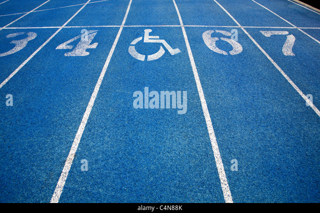 Handicap wheelchair icon superimposed on top of running track. - Stock Image