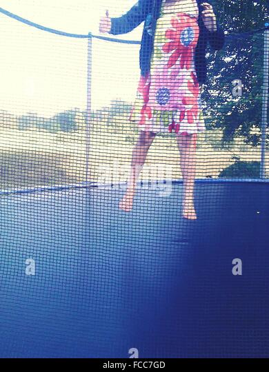 Low Section Of A Woman Jumping On Trampoline Against Landscape - Stock Image