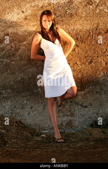 Young woman leaning against the wall - Stock Image