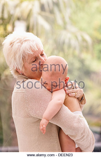 Grandmother holding and kissing baby - Stock Image