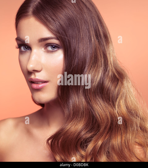 Beauty portrait of a young woman with beautiful long wavy brown hair - Stock Image