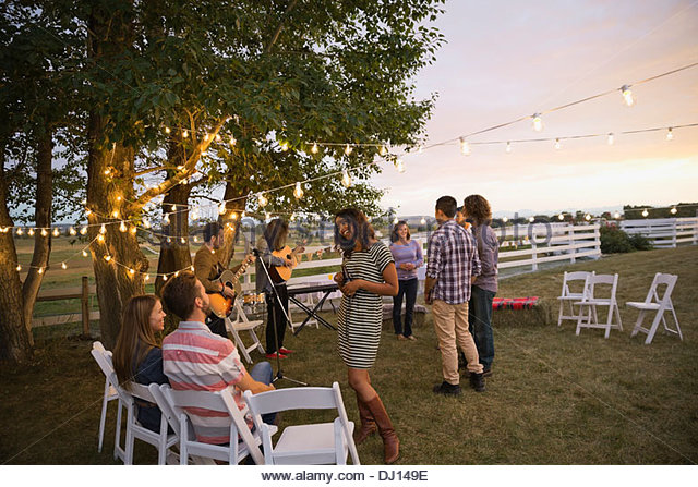 Friends enjoying outdoor farm party - Stock Image