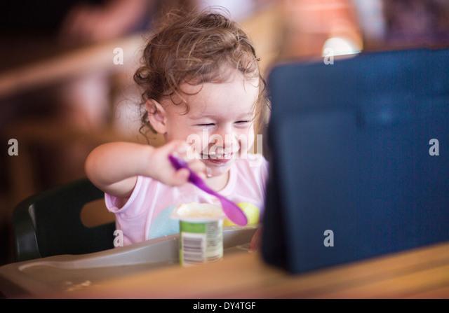 Toddler eating yogurt and using digital tablet - Stock Image