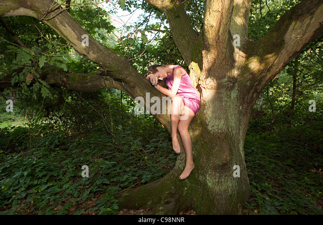 Young woman draped old oak tree - Stock Image