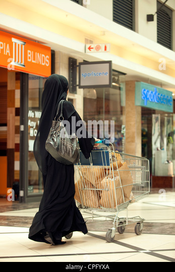Rear view of arab woman with shopping cart walking at the mall. - Stock Image