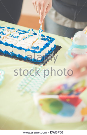 Close up of mature woman slicing birthday cake - Stock Image