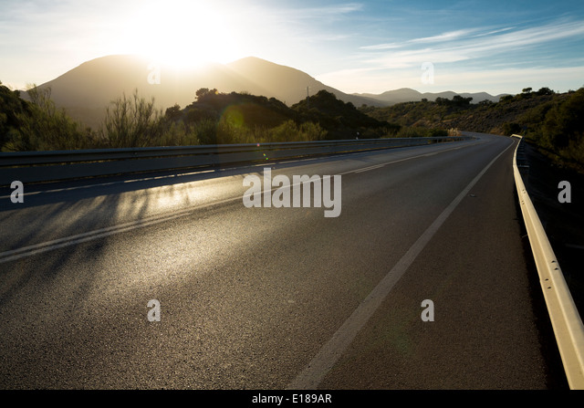 Sun shining over mountains and open road - Stock Image