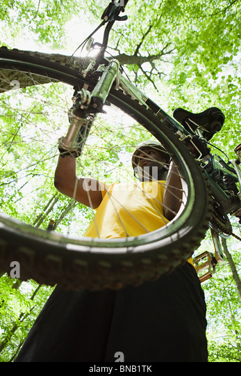 Male cyclist carrying bike in forest - Stock Image