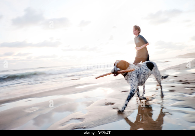A young boy and a dog with a stick in his mouth   run along a quiet beach in Mexico. - Stock Image
