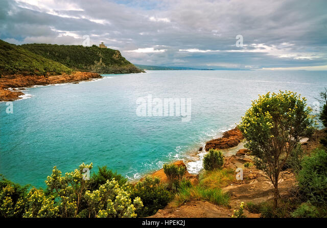 Cliff rock and building on the sea on sunset. Leghorn coast, Tuscany riviera, Italy, Europe. - Stock Image