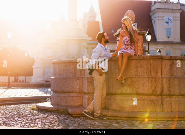 Young couple dating and flirting by fountain in town - Stock Image