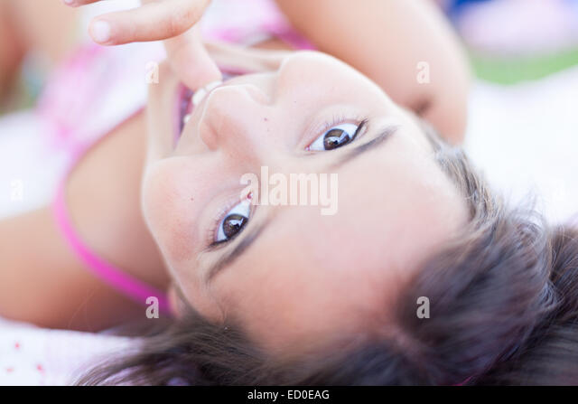 Close-up of girl (6-7) lying on back and looking at camera - Stock Image