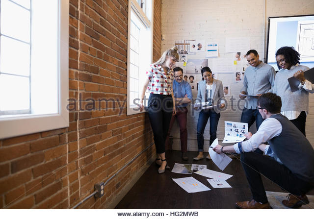 Designers meeting and brainstorming reviewing proofs in conference room - Stock Image