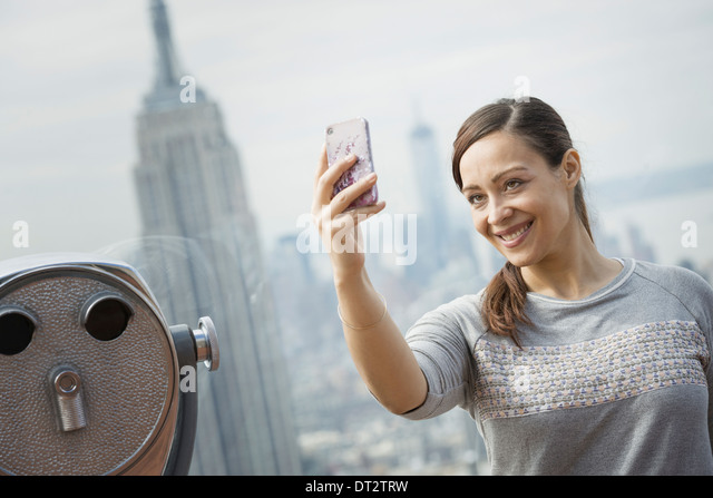 View over cityA woman using her smart phone to take a photograph - Stock Image
