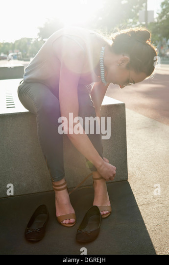 Germany, Berlin, Potsdam Square, young woman tying up her high heels - Stock Image