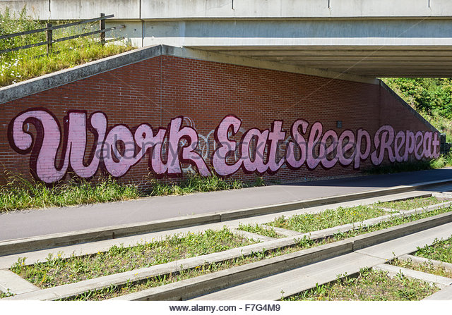 Graffiti saying work, eat, sleep, repeat on a bridge over the guided busway near Longstanton in Cambridgeshire - Stock Image