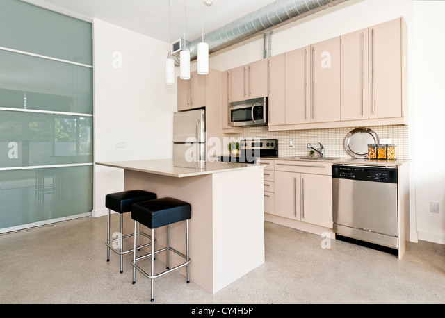 Kitchen in modern loft condo with island and stainless steel appliances - Stock Image