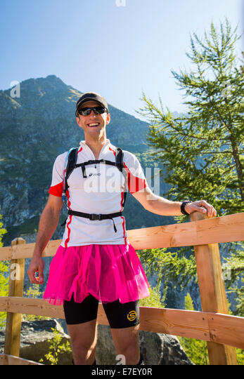 A trail runner in the French Alps on his stag holiday, wearing a pink skirt. - Stock Image