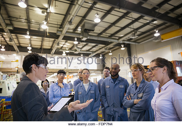 Manager with digital tablet leading meeting in factory - Stock Image