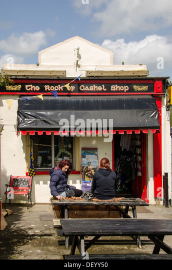 Two women sitting outdoors on wooden table at tourist store at St. Patrick's Rock of Cashel medieval complex, - Stock Image