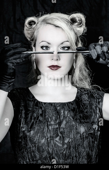 a beautiful woman from the 40s is holding a broken bar in front of her face - Stock Image