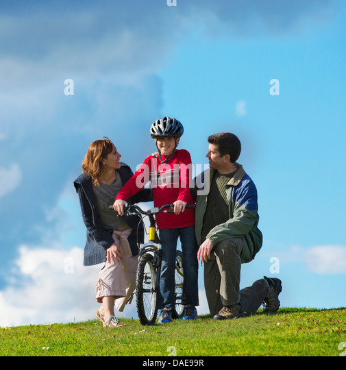 Mother and father encouraging son to ride bicycle - Stock Image