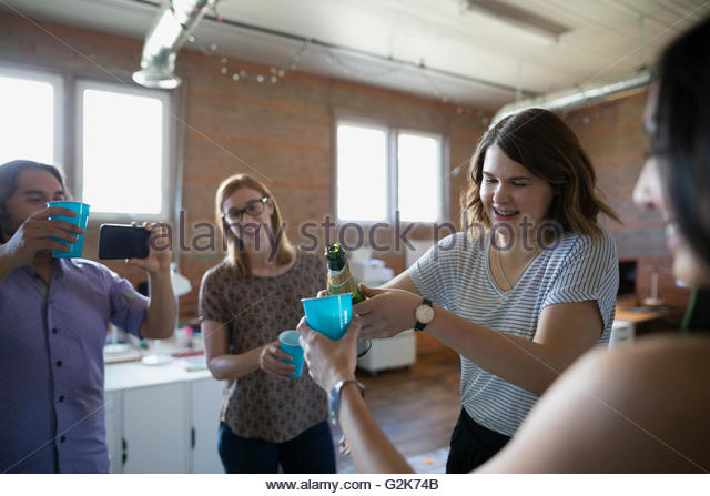 Creative business people celebrating pouring champagne in office - Stock Image