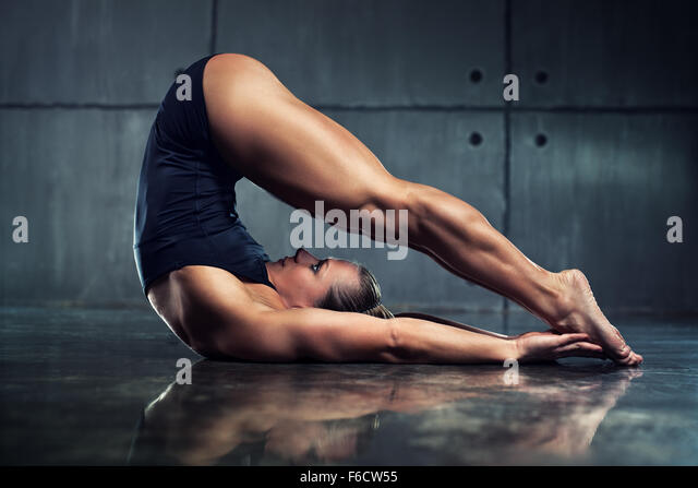 Strong woman bodybuilder stretching upside down in urban interior. - Stock Image