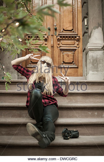 Fun young woman hiding behind her long blond hair on steps - Stock Image