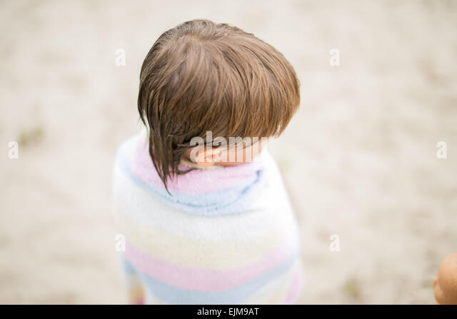 Little boy wrapped in towel at the lake on hot summer day. Having fun during vacation. - Stock-Bilder