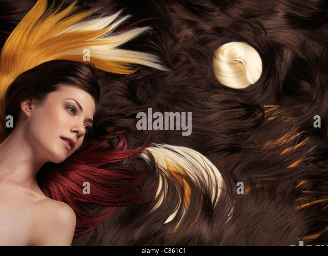 Artistic photo of a beautiful woman with long brown hair and artistically arranged colorful hair extensions - Stock-Bilder