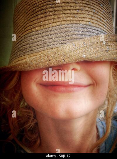 Young girl wearing hat over her eyes and smiling - Stock Image