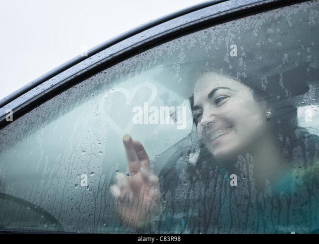 Teenage girl drawing on wet car window - Stock Image