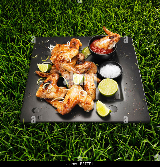 Barbecued chicken wings with spring onions, lime, salt and ketchup on a grass background. - Stock Image