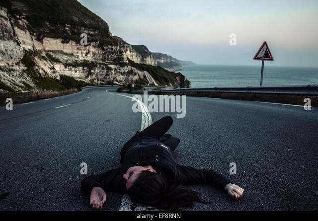Woman lying down in middle of road - Stock-Bilder