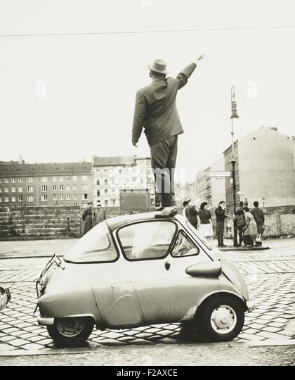 A man standing on top of a small three-wheeled car waving across the newly constructed Berlin Wall. This West Berliner - Stock-Bilder