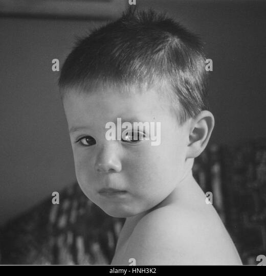 Head and shoulder shot of toddler looking sad anxious downcast forlorn lonely in black and white - Stock Image