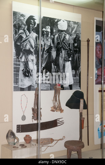 Display case of beaded leather belt worn by Boran men for the naming of their sons with photographs of Boran man - Stock Image
