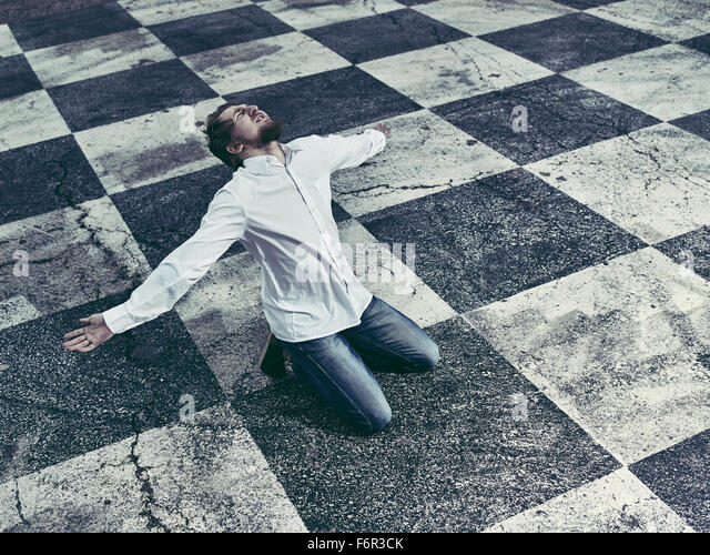 Conceptual, humble man and checkered ground - Stock Image