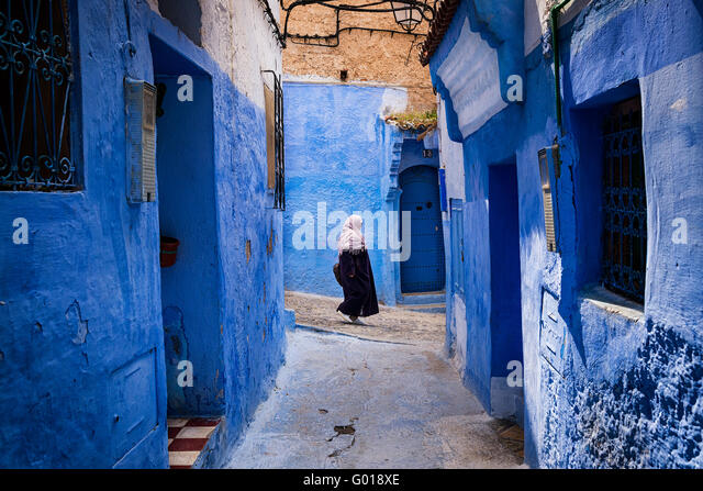 Chefchaouen, Morocco - April 10, 2016: A woman walking in a street of the town of Chefchaouen in Morocco. - Stock Image