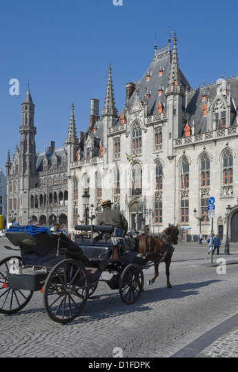 A horse drawn carraige drives past the Provincial Court Building in the Market Square, Brugge, Belgium, Europe - Stock-Bilder
