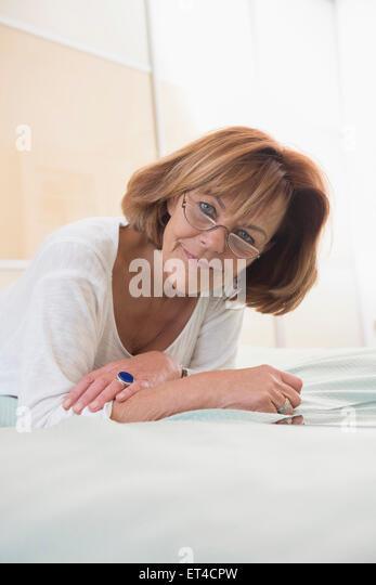 Portrait of senior woman lying on bed, Munich, Bavaria, Germany - Stock-Bilder