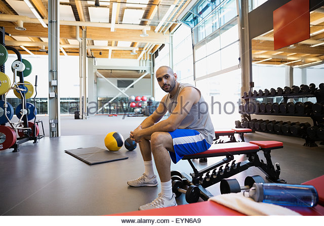 Portrait serious man resting on weightlifting bench gym - Stock Image