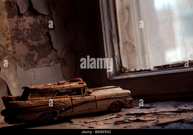 Rusty toy car in an abandoned house - Stock Image
