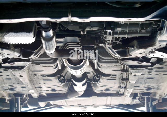 Underside of vehicle on lift in mechanics garage - Stock Image