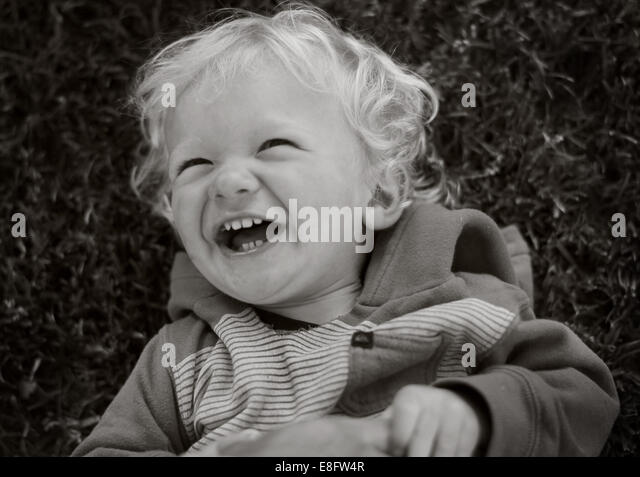 Toddler lying on grass laughing - Stock Image