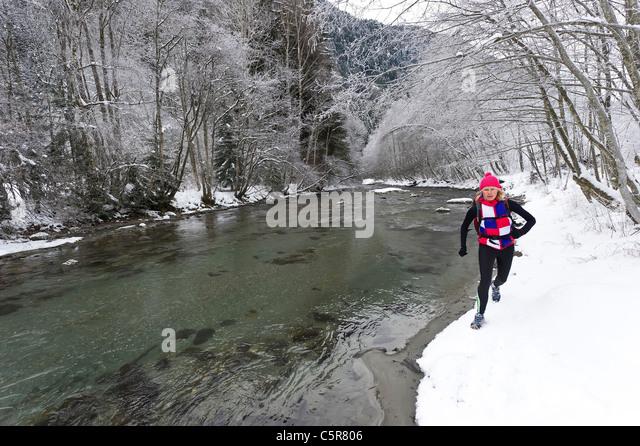 A jogger running alongside a snowy alpine river. - Stock-Bilder