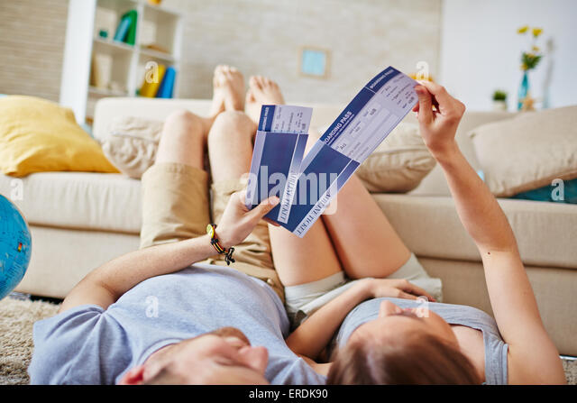 Restful couple with air tickets lying on the floor at home - Stock Image